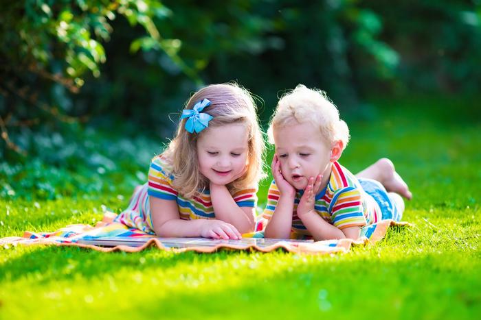 enfants lisant sur l'herbe