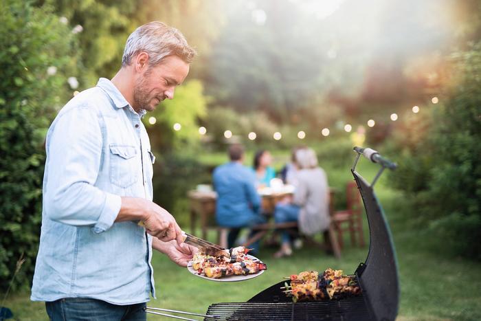 Homme plus âgé à l'aide d'un barbecue