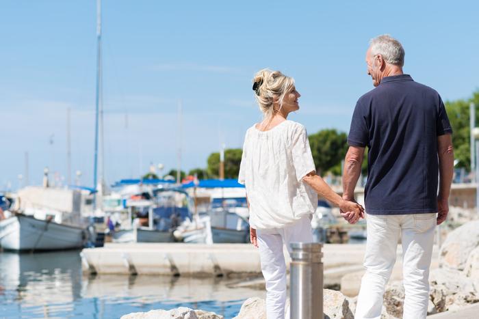 couple plus âgé marchant le long d'un port